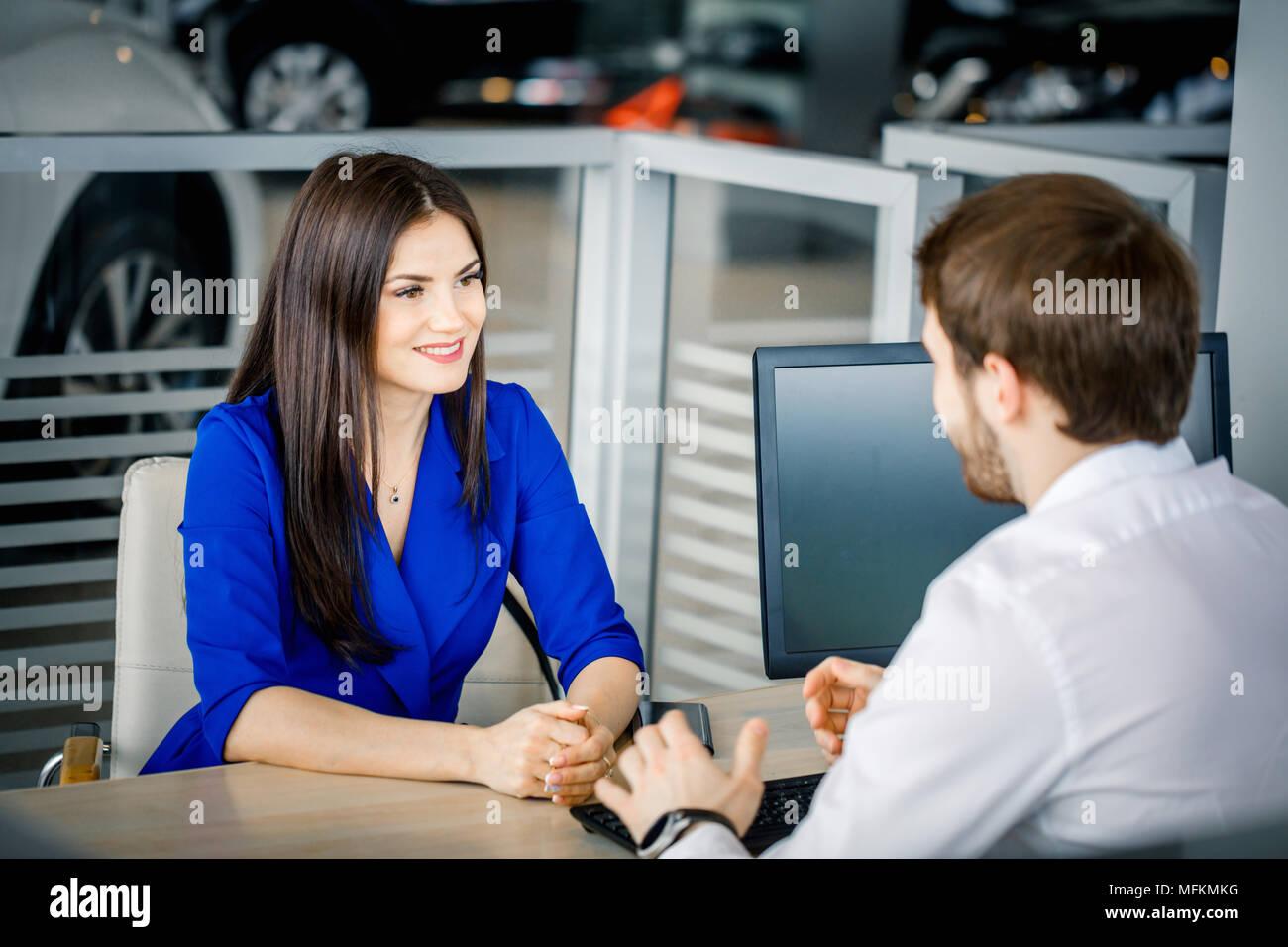 Schöne brünette Mädchen Hören zu einem Sales Agent über die Stärken der ausgewählten Auto an Auto Dealership Büro erklären Stockbild