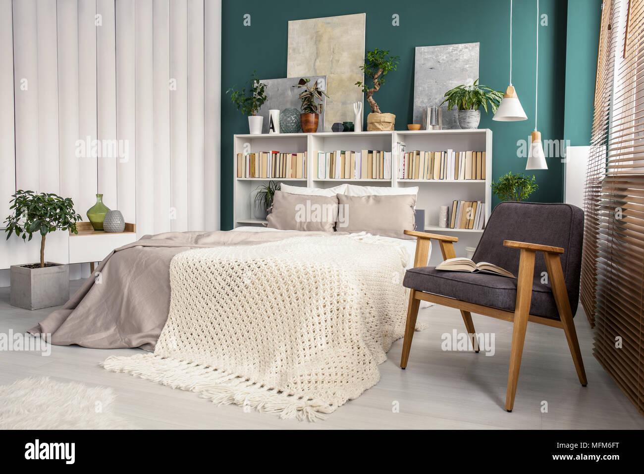 Weiß Und Grün Schlafzimmer Innenraum Mit Einem Strick Decke Auf Beige Bett  Zwischen Vintage, Grau Sessel Und Rohre An Der Wand