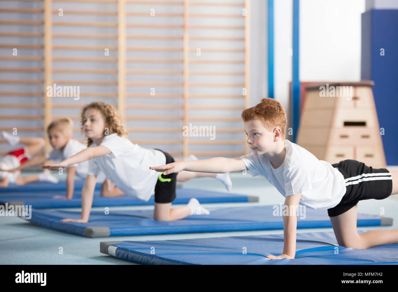 Gruppe von Kindern Gymnastik auf blauen Matten im Sportunterricht der Klasse in der Schule Stockfoto