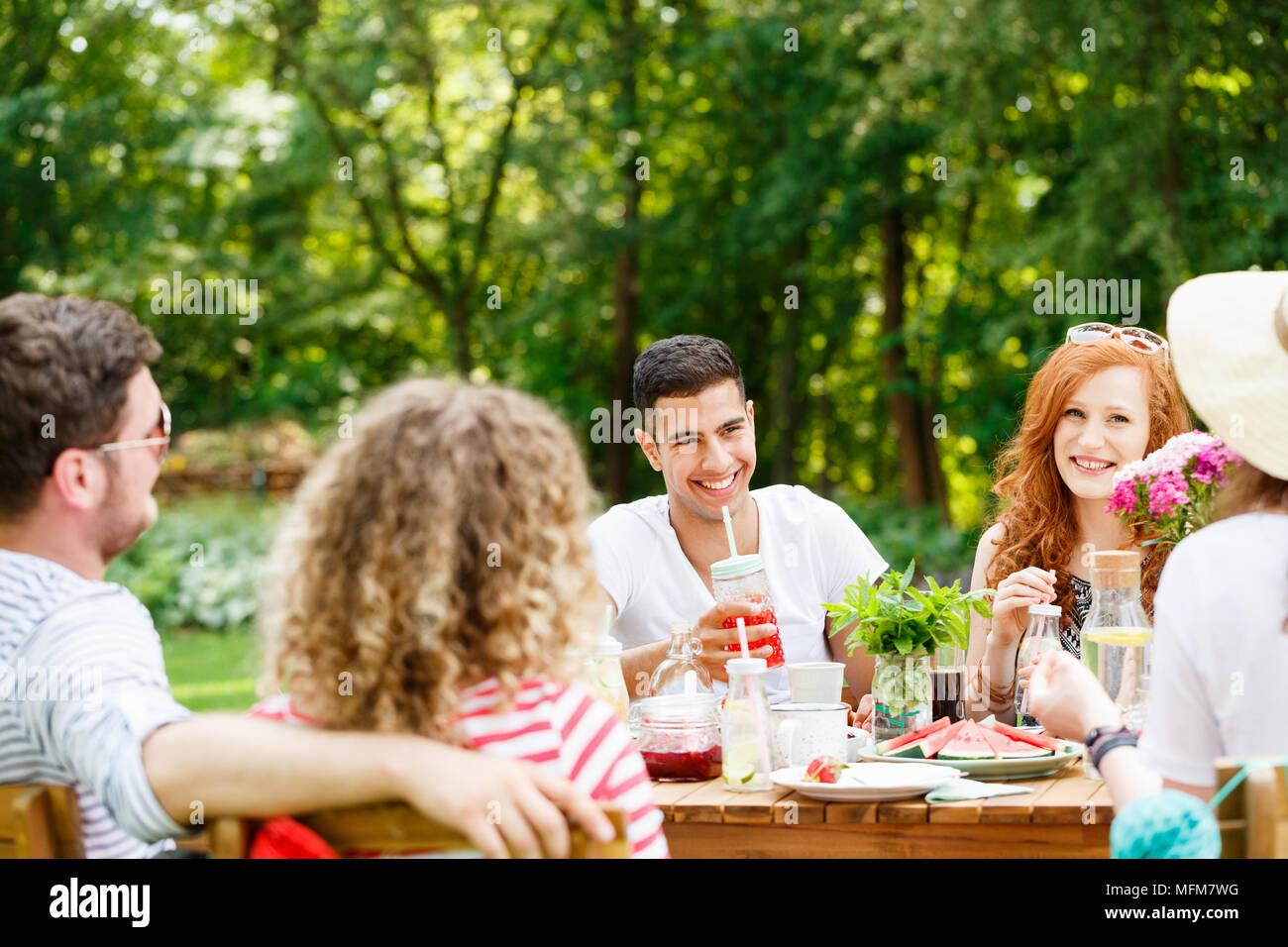 Junge Leute lachen, essen und sprechen an einem sonnigen Tag im Garten Stockbild
