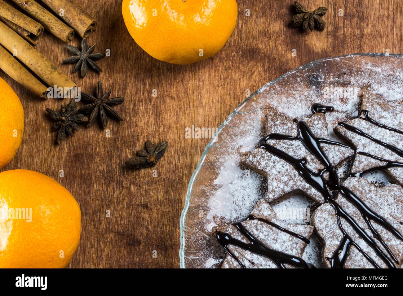 Ingwer Kekse mit Schokolade auf einem hölzernen Hintergrund, Mandarine, Zimt Stockbild