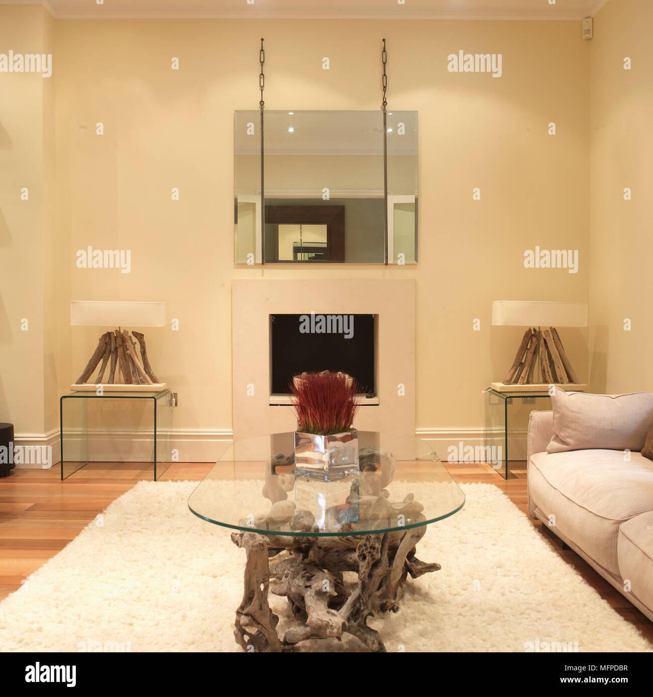 couchtisch aus glas oben auf treibholz auf weissen teppich in moderne wohnzimmer