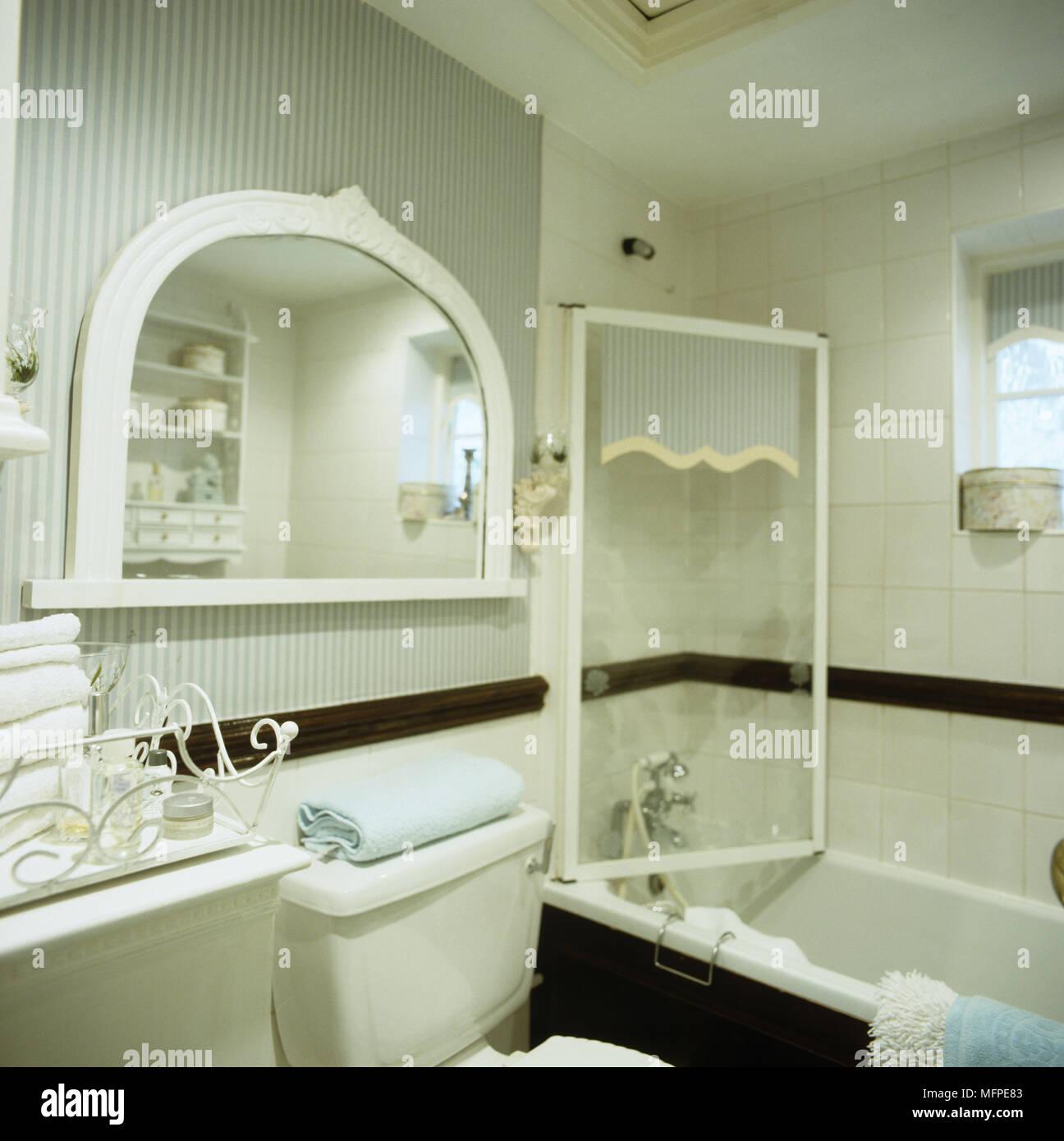 Ein traditionelles Bad mit blau gestreiften Tapeten und ...
