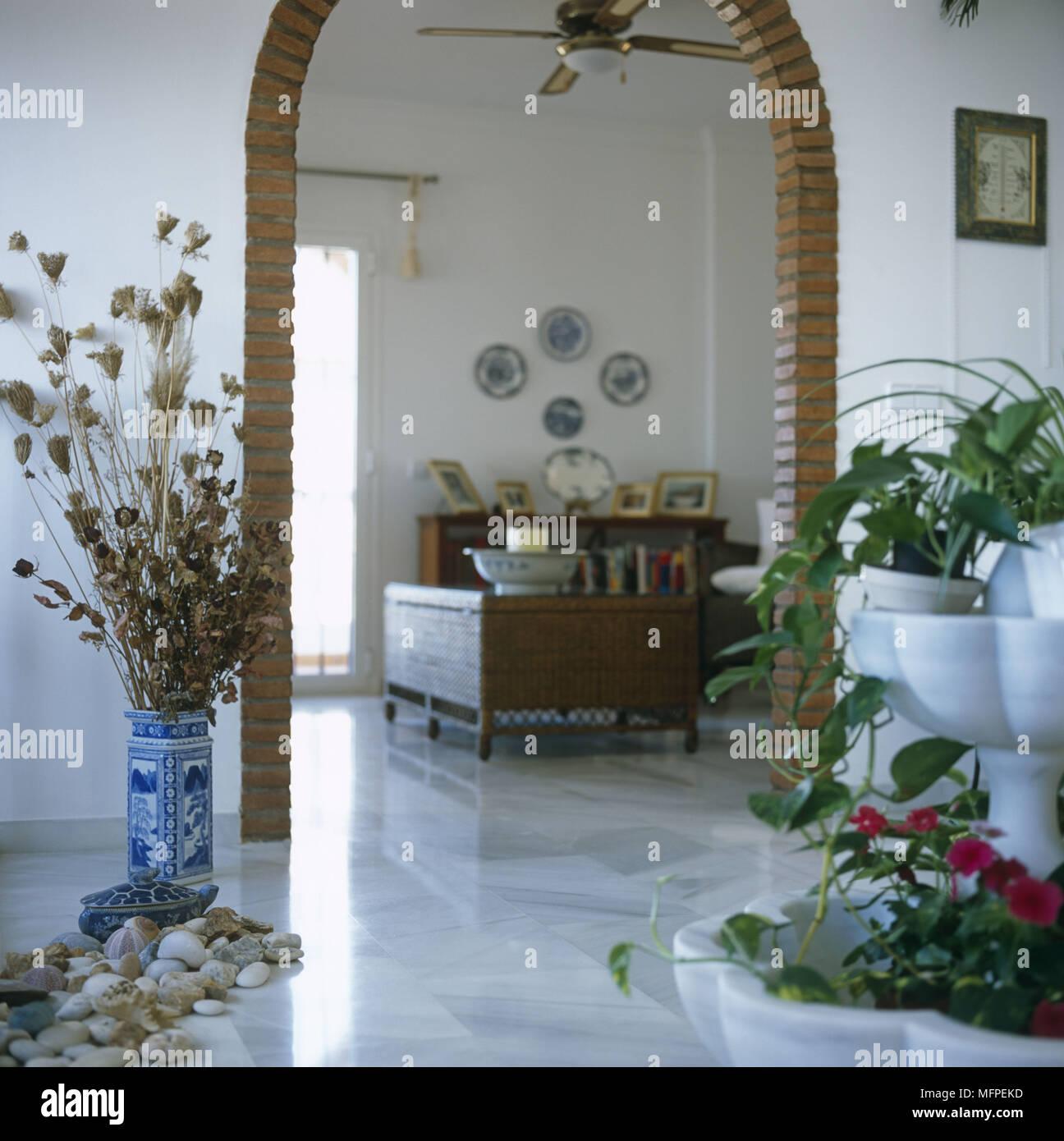 Der Blick Durch Einen Gemauerten Bogen Zu Einem Mediterranen Stil Wohnzimmer  Mit Marmorboden Mit Einer Anzeige Der Steine Und Muscheln Auf Den Boden.