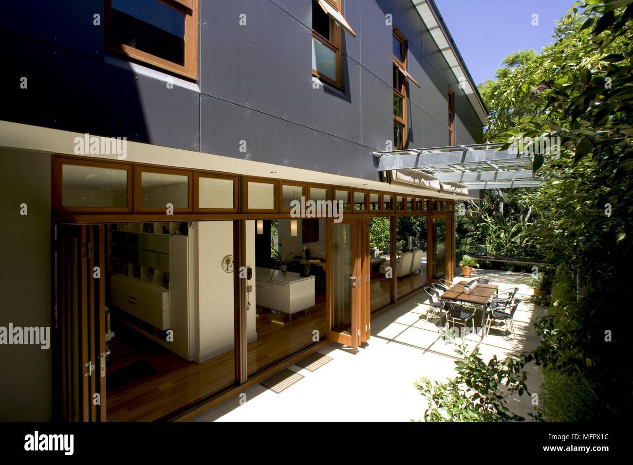 Von außen ein modernes Haus mit Tisch und Stühlen auf der Terrasse ...