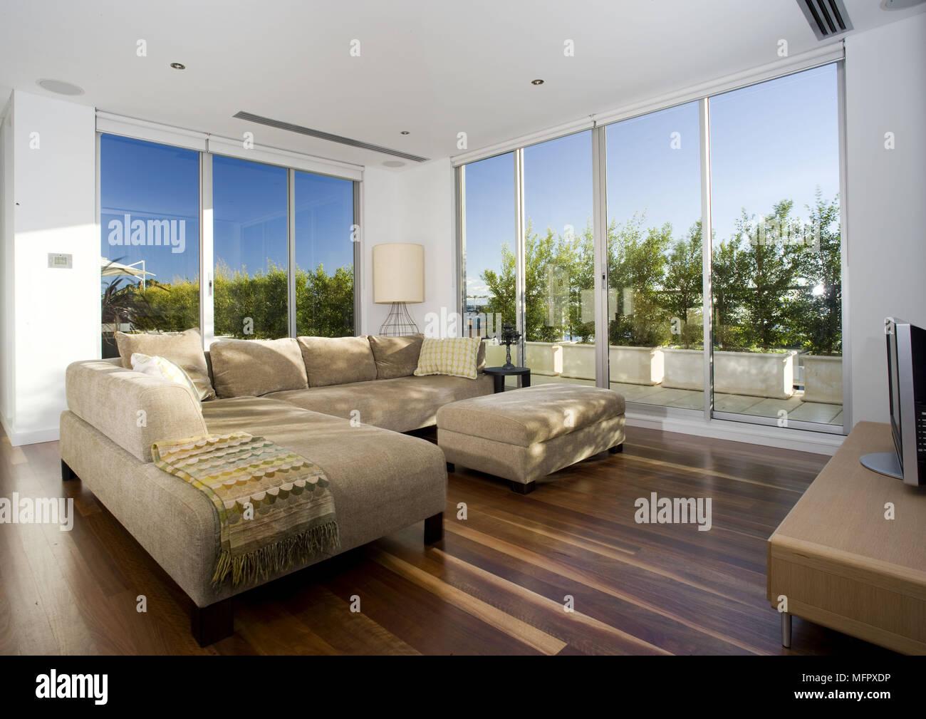 Gepolstertes sofa mit ottomane in modernen geräumigen wohnzimmer