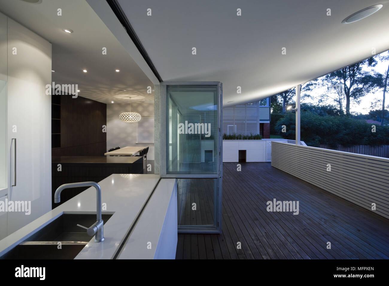 Blick von der Terrasse in die moderne offene Küche und Esszimmer, in ...