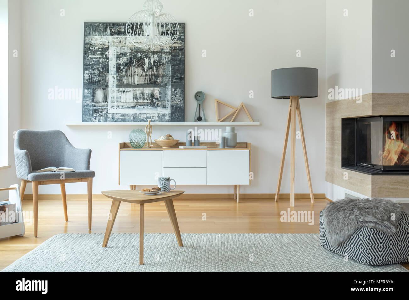 Perfekt Gemusterte Puff In Der Nähe Von Kamin Und Grau Lampe In Scandi Wohnzimmer  Einrichtung Mit Sessel Und Malerei