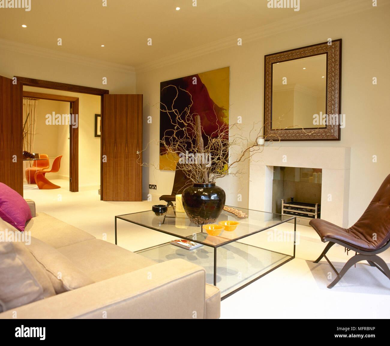 Wohnzimmer Mit Offenen Türen, Sitzecke Mit Glas, Couchtisch Und Einem  Großen Spiegel über Dem Kamin.