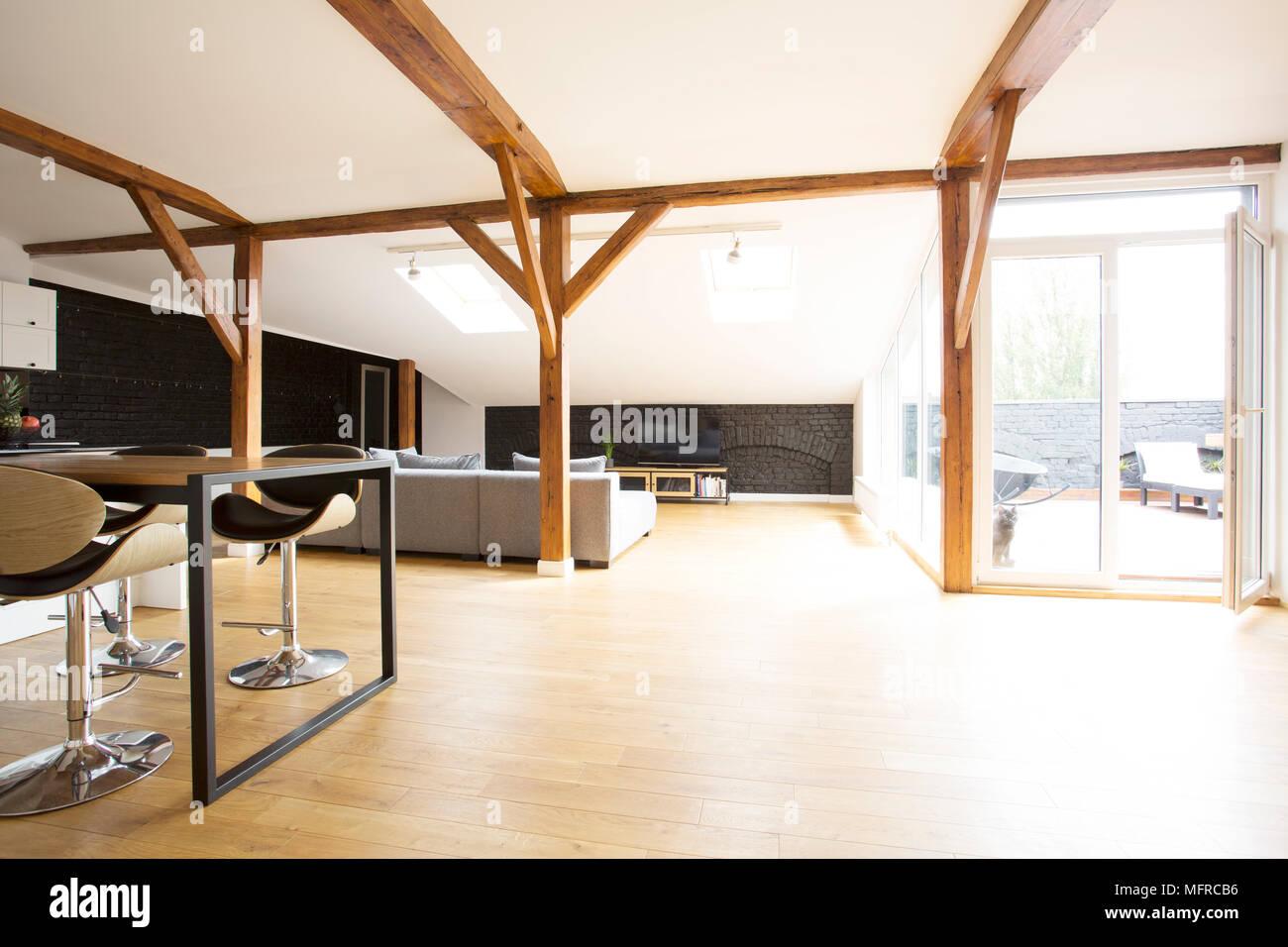 Geräumige Interieur Mit Holzboden, Barhocker, Tisch, Graue Sofa, Balken Und  Terrasse