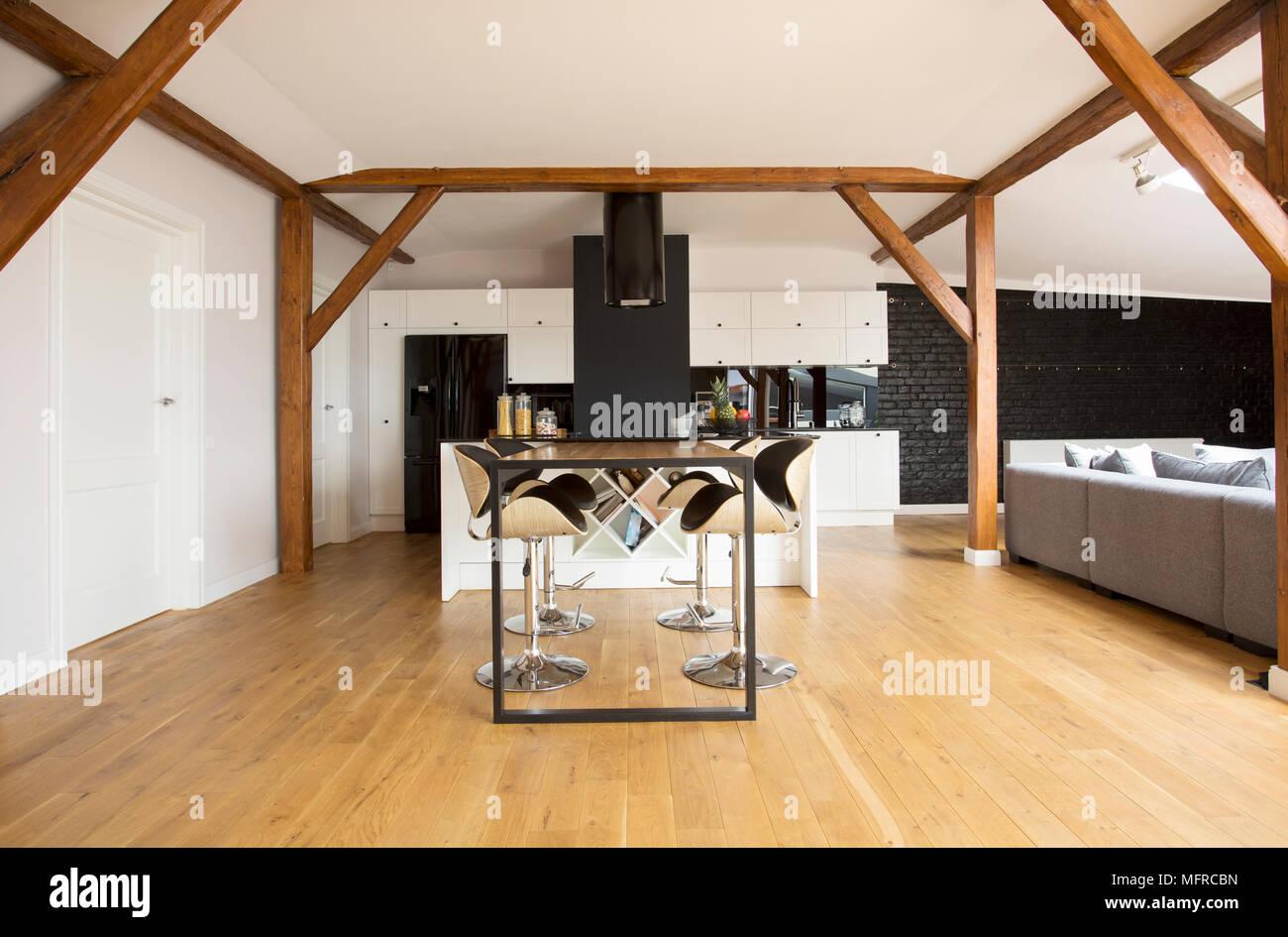 Modernen Barhockern Und Schwarzen Tisch Im Apartment Im Dachgeschoss  Interieur Mit Holzboden, Balken Und Grau Sitzgarnitur