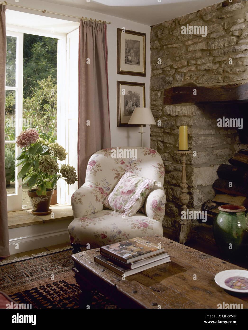 Landhaus Wohnzimmer Detail Mit Einem Offenen Fenster, Holz  Tisch, Einen  Geblümten Gepolstertem Sessel Neben Einem Stein Kaminecke.