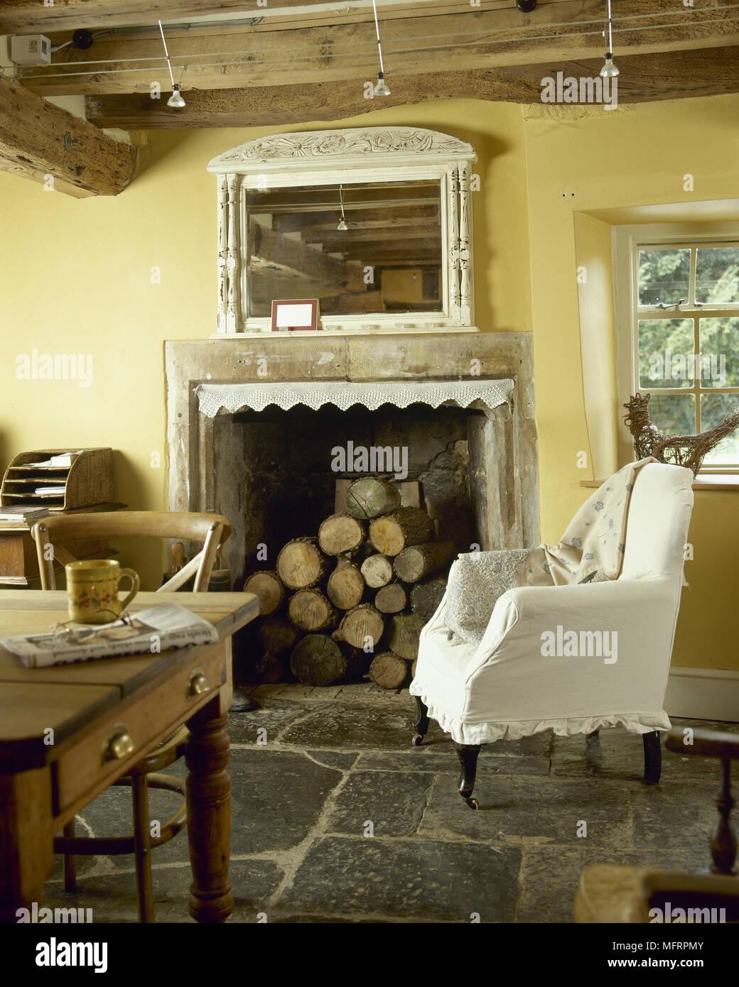AuBergewohnlich Land, Gelb Küche Mit Holzbalkendecke, Kamin Aus Stein Mit Gestapelten  Brennholz, Flagstone Boden Gefüllt, Und Einem Sessel.