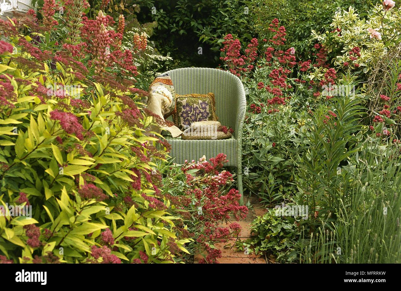 Ein Garten Detail A Lloyd Loom Korbsessel Unter Blumen Und Sträucher