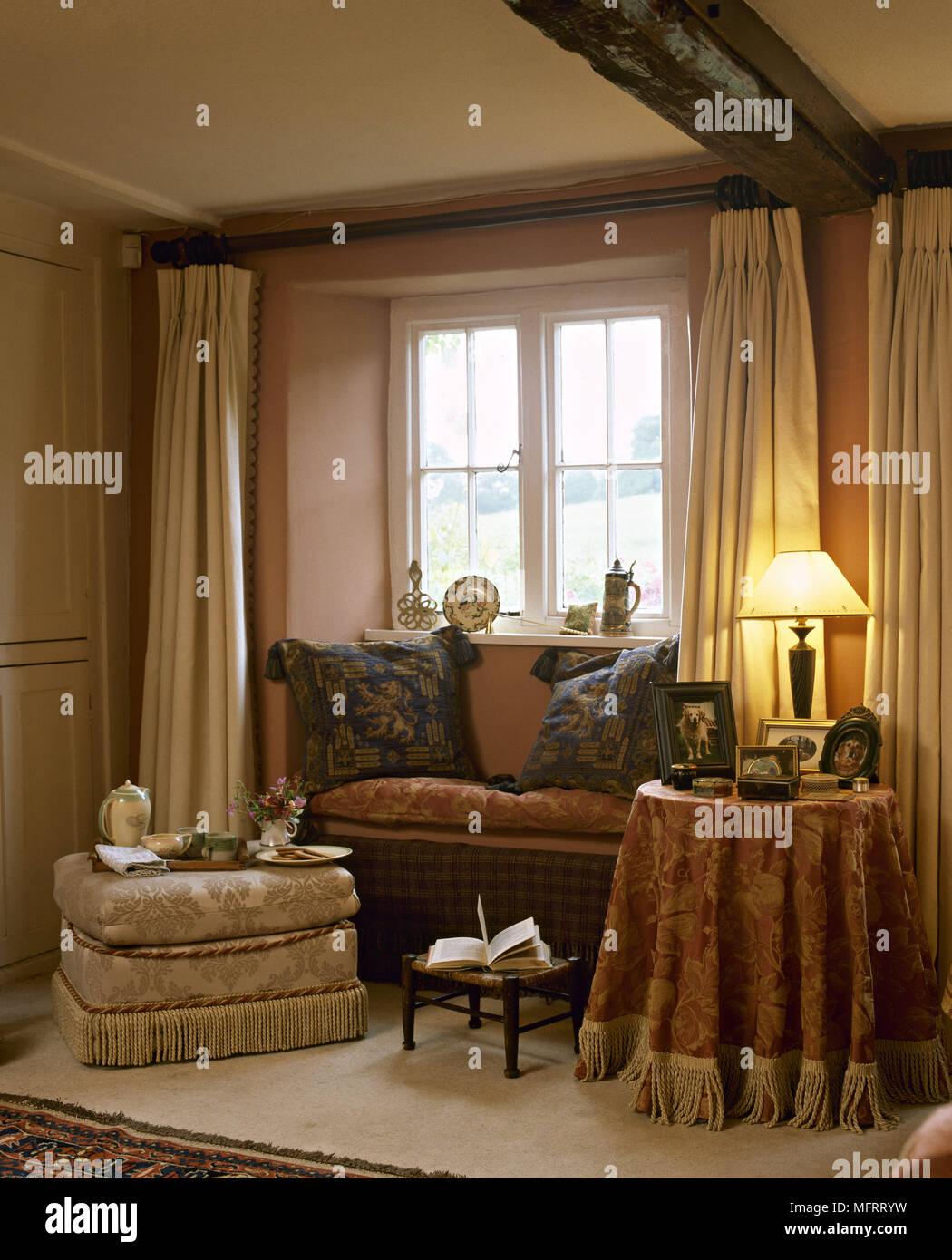 Landhausstil Wohnzimmer Mit Fenster Vorhänge Stoff überzogenen Tisch  Gepolsterten Hocker Und Holzbalken.