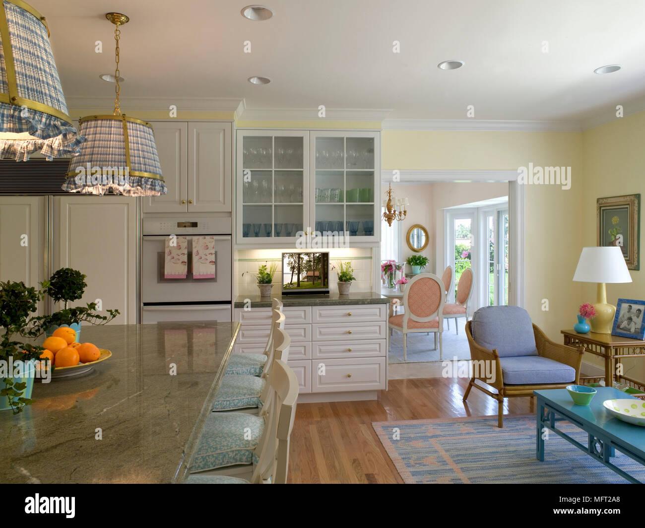 Eine moderne, offene Küche mit Essbereich, Tisch, Stühlen ...