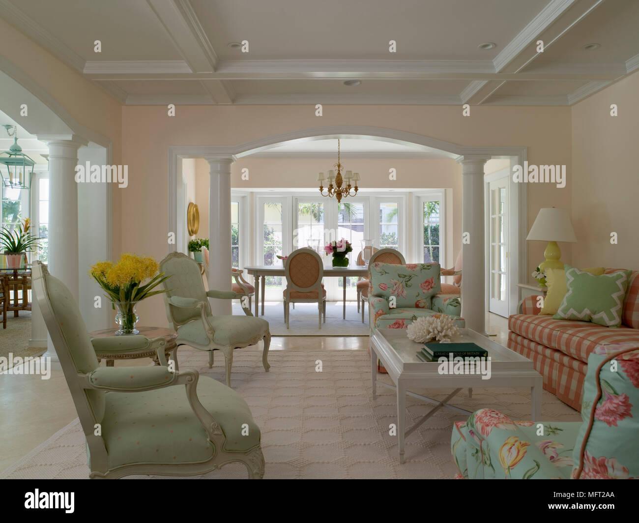 Ein Traditionelles Wohnzimmer, Balkendecke, Blick Durch Die Offenen  Torbogen, Esszimmer, Gepolsterte Stühle, Couchtisch, Beige Teppich.