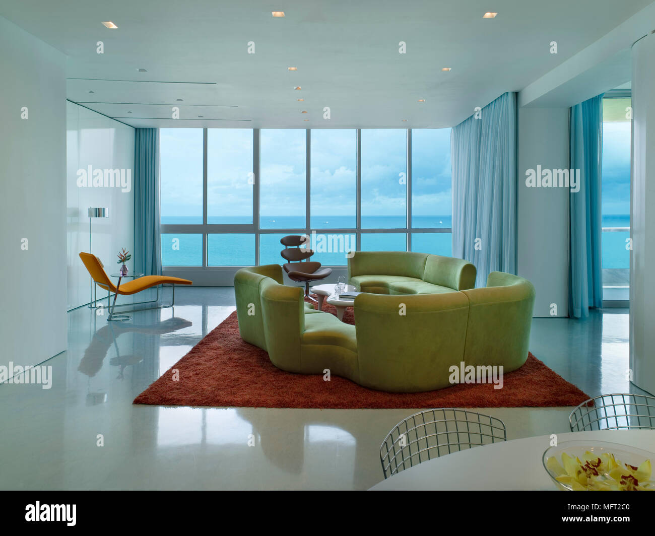 Ein Modernes, Retro Style Offene Wohnzimmer Mit Essbereich, Geschwungene,  Gepolsterten Sitzgelegenheiten, Roter Teppich, Mix Aus Designer Sitzmöbel,  ...