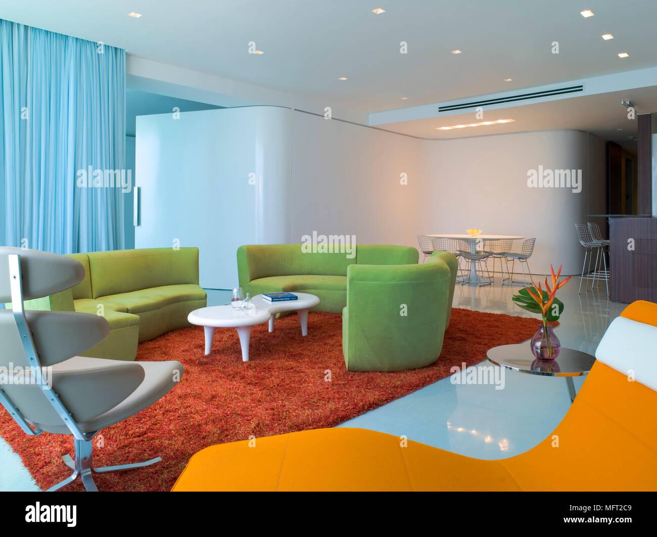 Ein Modernes, Retro Style Offene Wohnzimmer Mit Essbereich, Geschwungene,  Gepolsterten Sitzgelegenheiten, Geformt Geschwungene Wand, Roter Teppich,  ...