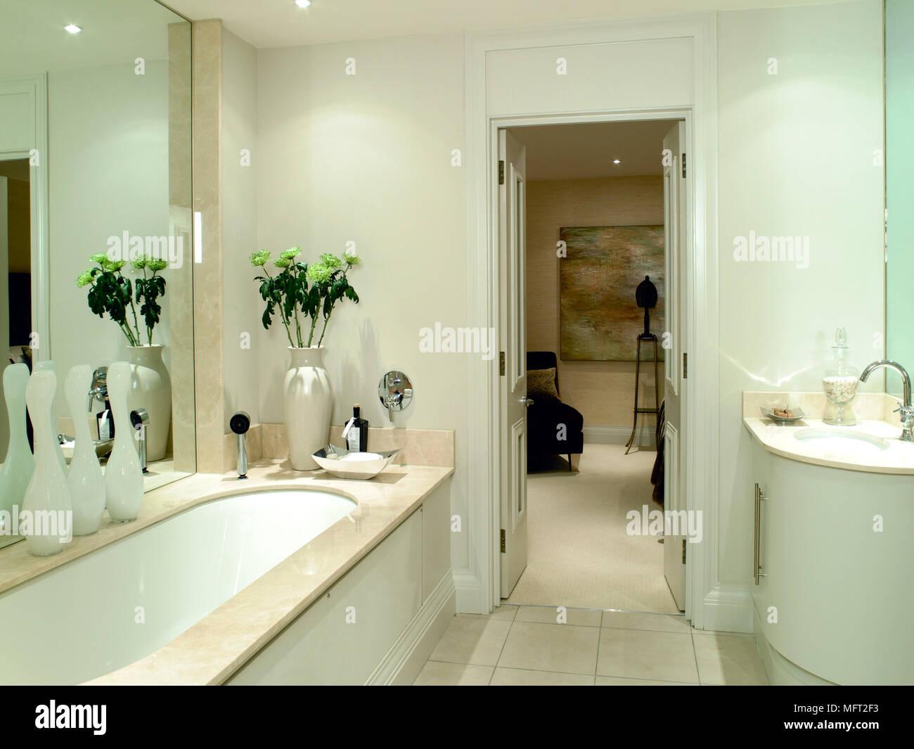 Modernes Badezimmer Mit Waschbecken In Gekrümmten Vanity Set, Badewanne Mit  Marmor Umgeben, Große Spiegel, Und Eine Offene Tür Zu Einem Angrenzenden  Raum.