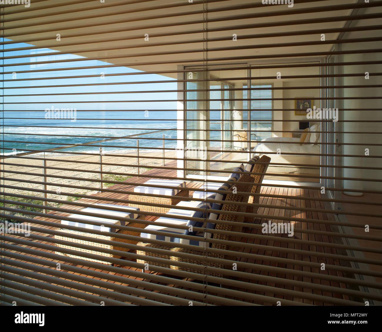 Blick durch die Jalousien auf Terrasse mit Holzterrasse Korbstühlen ...