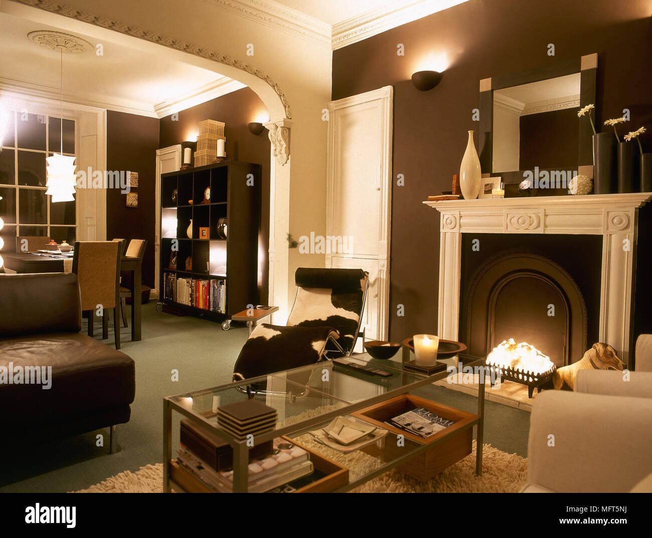 Ein Modernes, Offenes Wohnzimmer Mit Essbereich, Kamin, Couchtisch Aus  Glas, Le Corbusier Sessel,