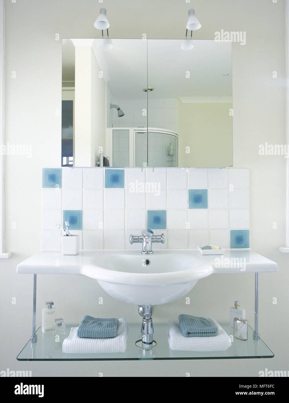 Gefliestes Badezimmer Mit Waschbecken, Glas Regal An Der Wand, Dekorative  Fliesen Montiert, Und Einen Spiegel.