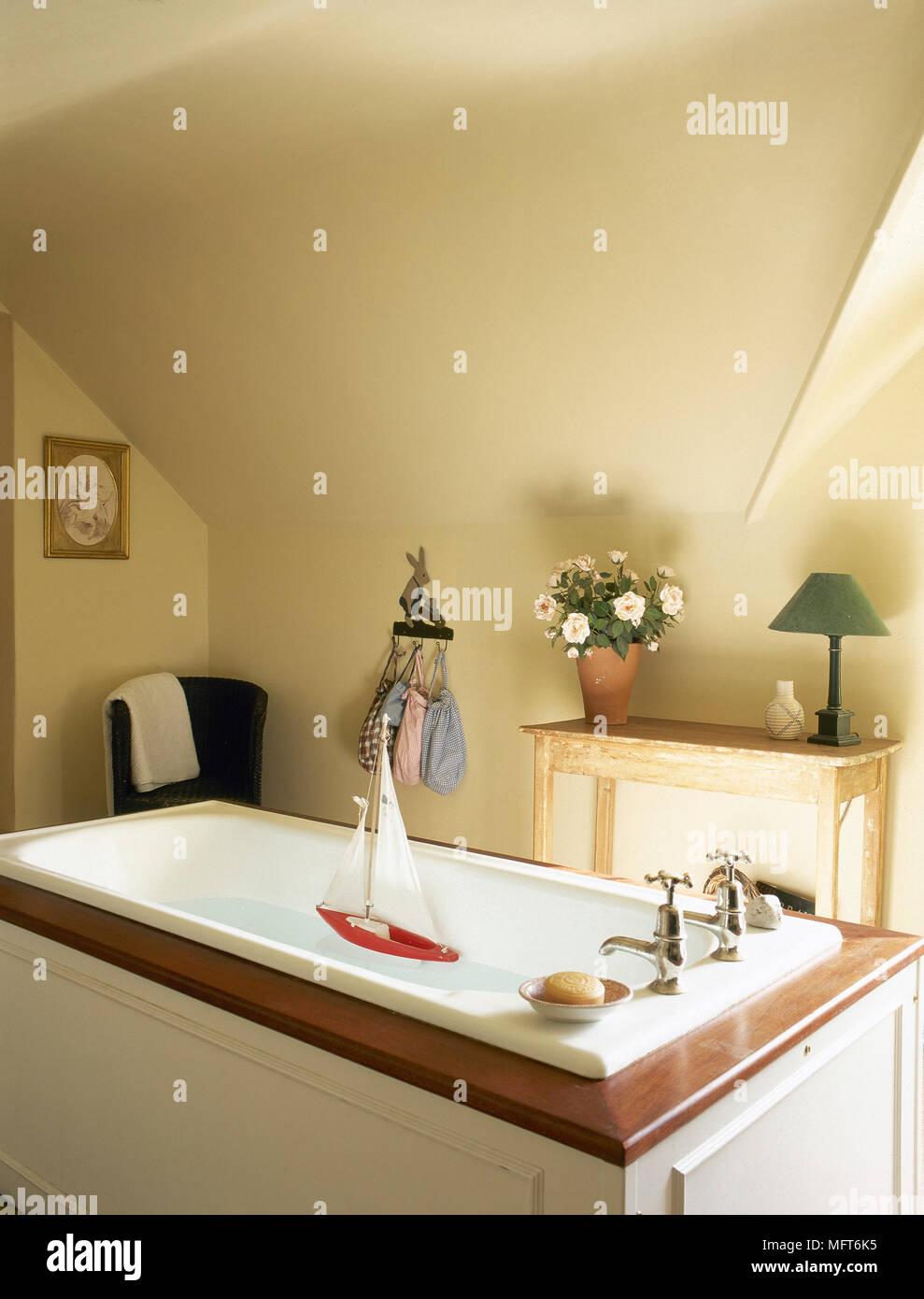 Land Gelb Bad Mit Einer Dachschräge, Holztisch, Und Ein Segelboot Schwimmen  In Eine Badewanne Mit Holz Umgeben.