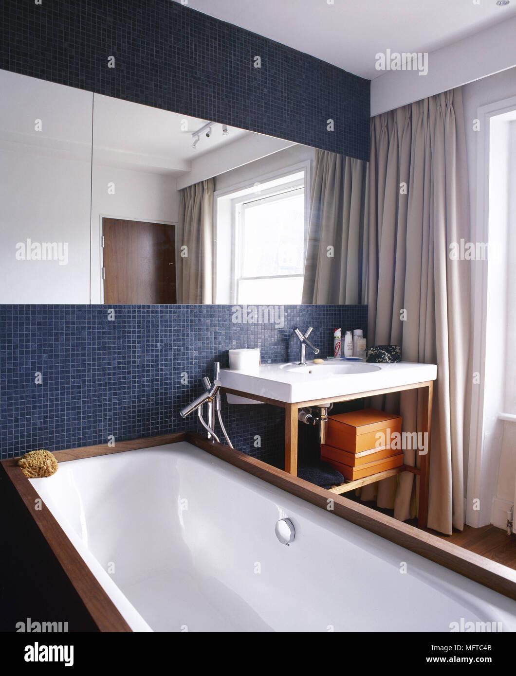 Modernes Badezimmer Mit Mosaik Fliese Mauer, Großer Spiegel, Waschbecken  Auf Einem Stand Aus Holz, Und Badewanne.