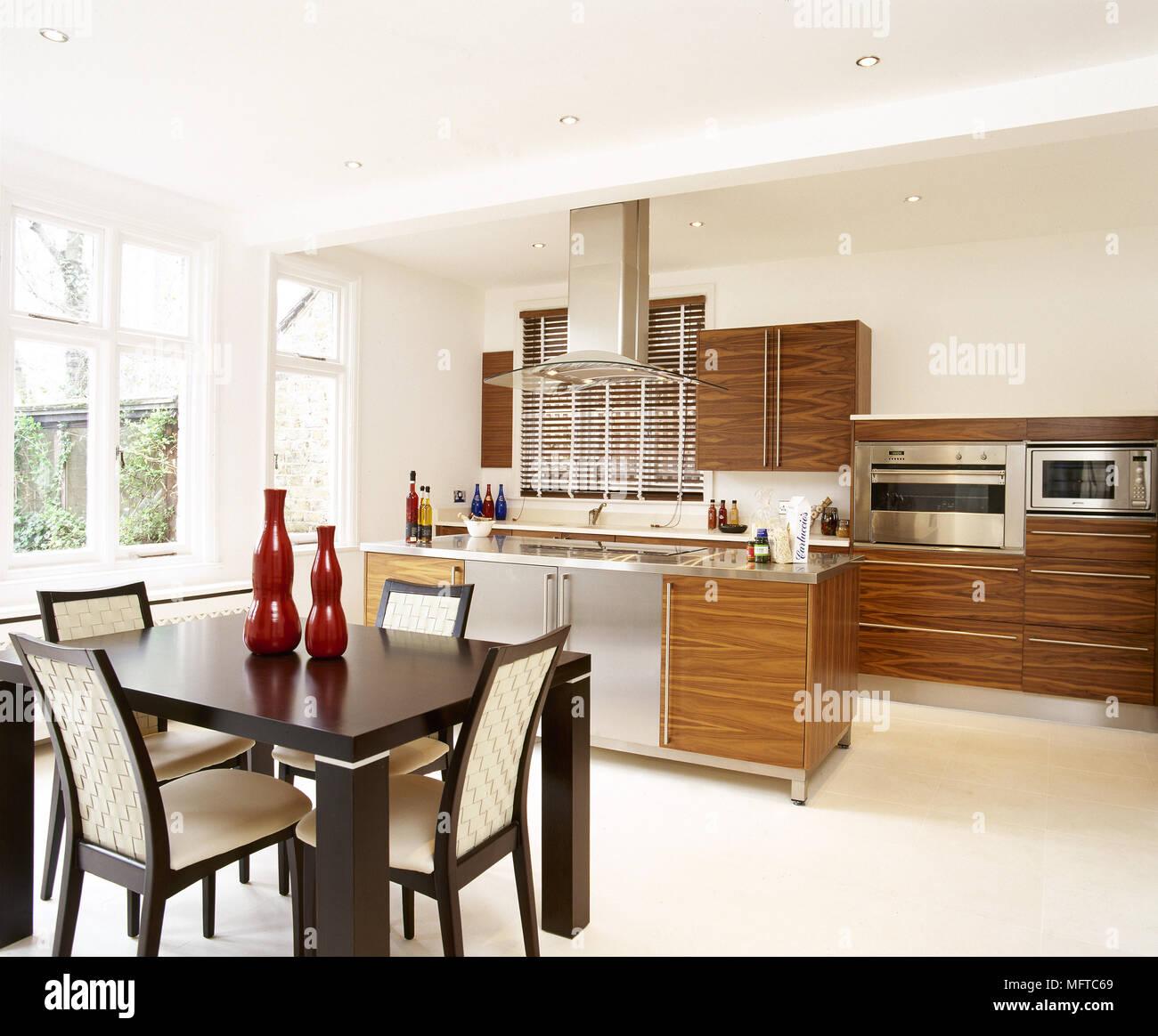 Leichte Küche Und Essbereich Mit Holzgehäuse, Zentrale Insel, Und Eine  Schwarze Holz Tisch Und Stühlen.