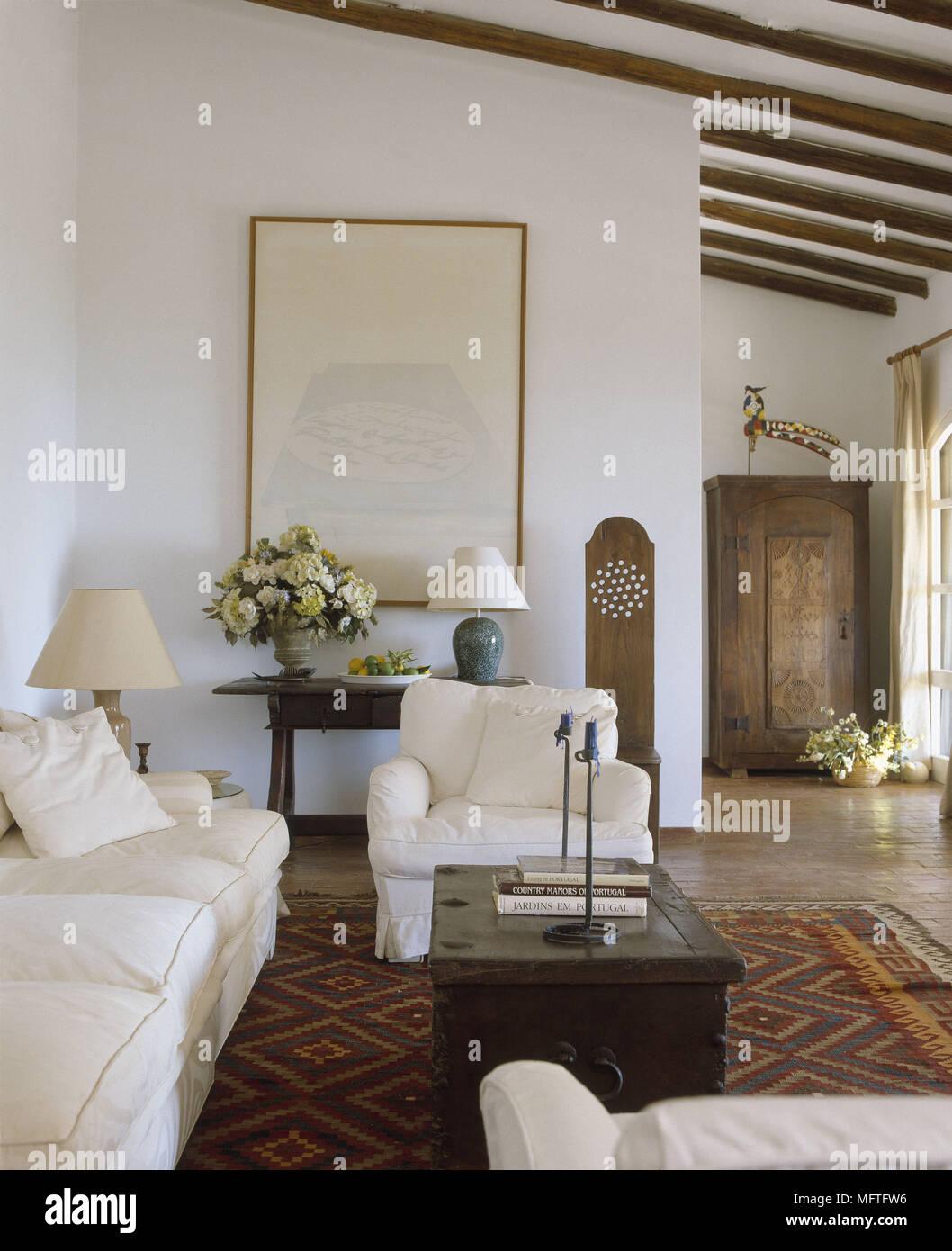 Traditionelle Zimmer Mit Weißen Wänden Schräge Balkendecke Sofa Sessel Und  Wall Art.