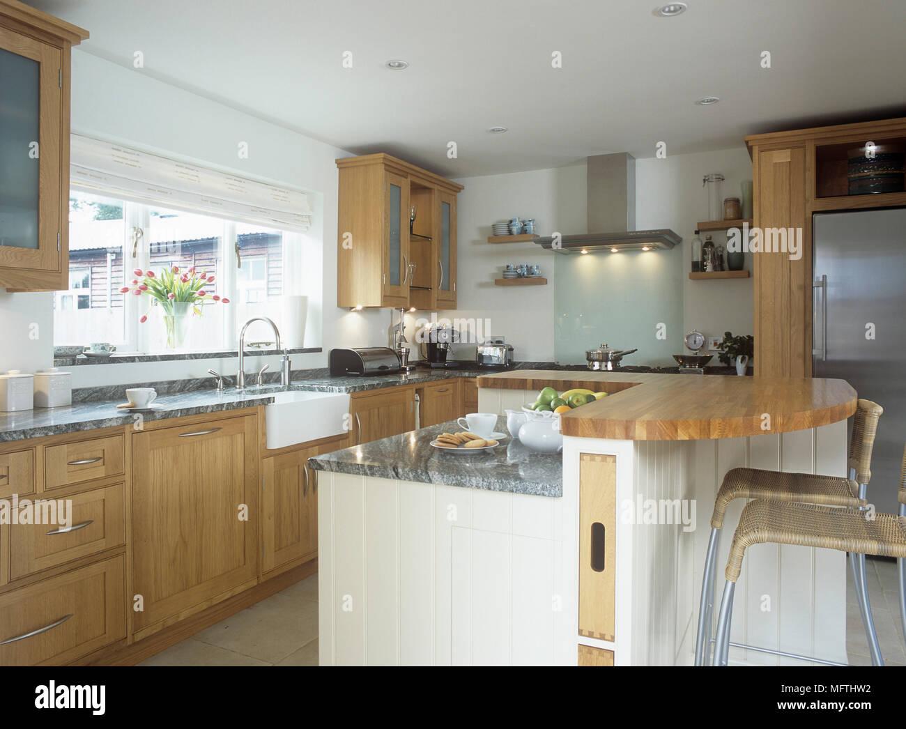 Eine moderne Küche mit Holzschränken, zentrale Insel mit Frühstück ...