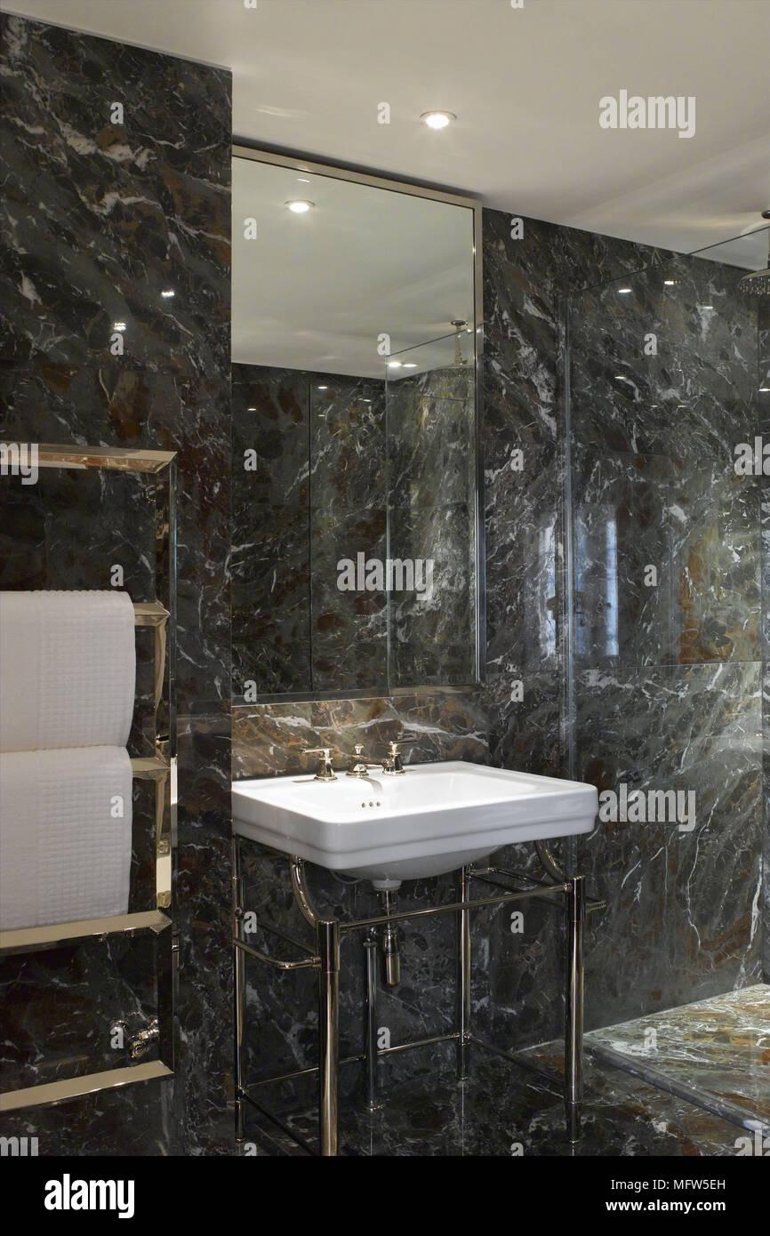 Ein Badezimmer mit Wänden aus Marmor und Gold Armaturen ...
