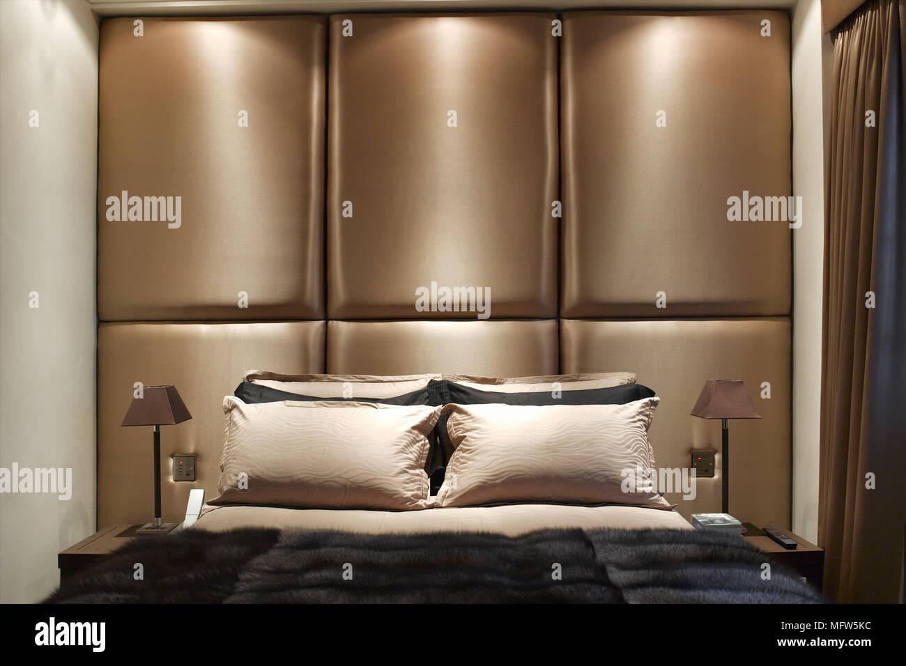Ein Modernes Schlafzimmer Mit Einer Gepolsterten Holzgetafelten Wand Uber Ein Doppelbett Mit Beleuchtung Von Oben Stockfotografie Alamy
