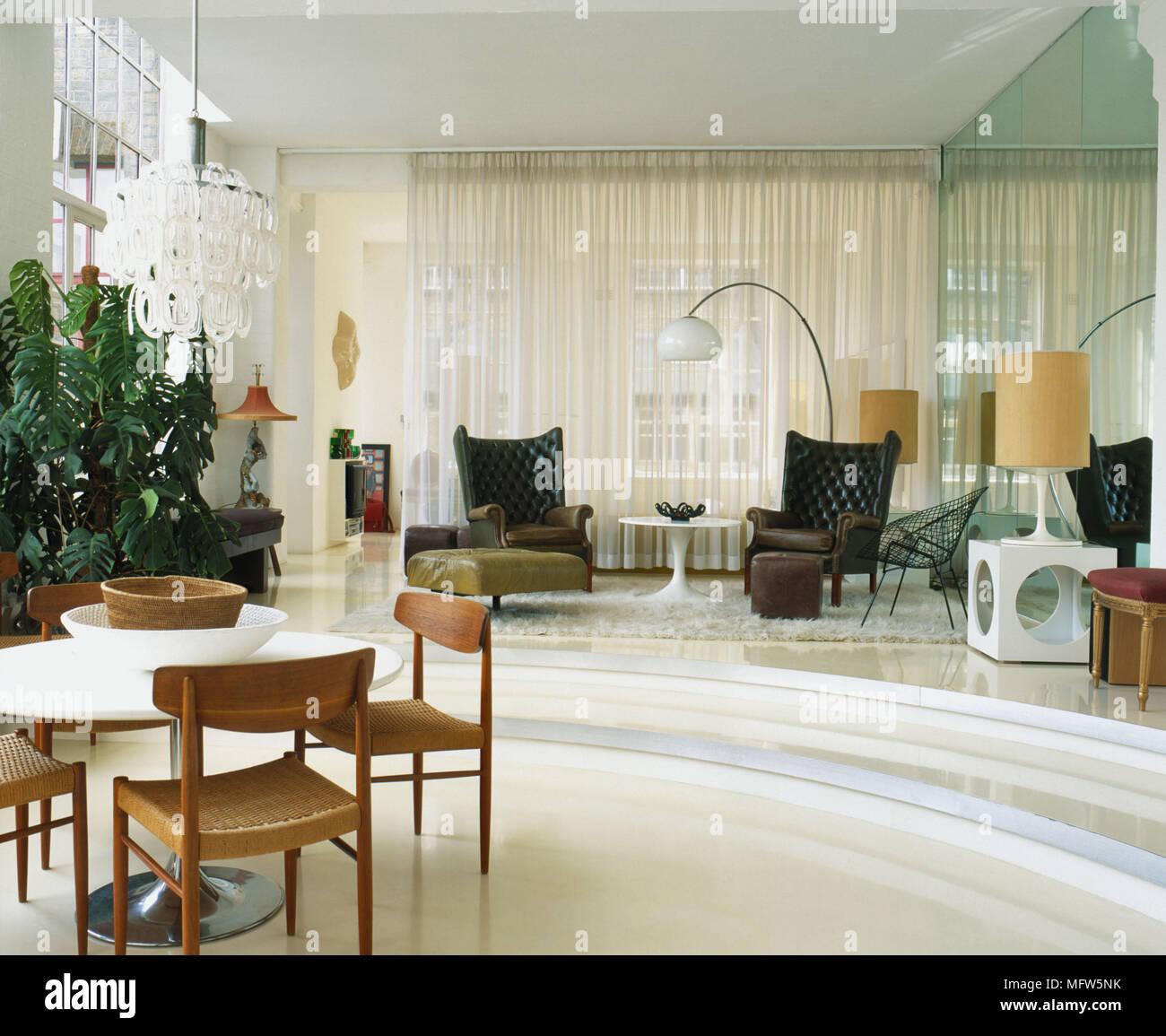 Eine Moderne Offene Wohnzimmer Mit Essbereich Runden Tisch Und Stühle Aus  Holz Retro Stil Seite Tischleuchte Gardinen Pendelleuchte Sessel