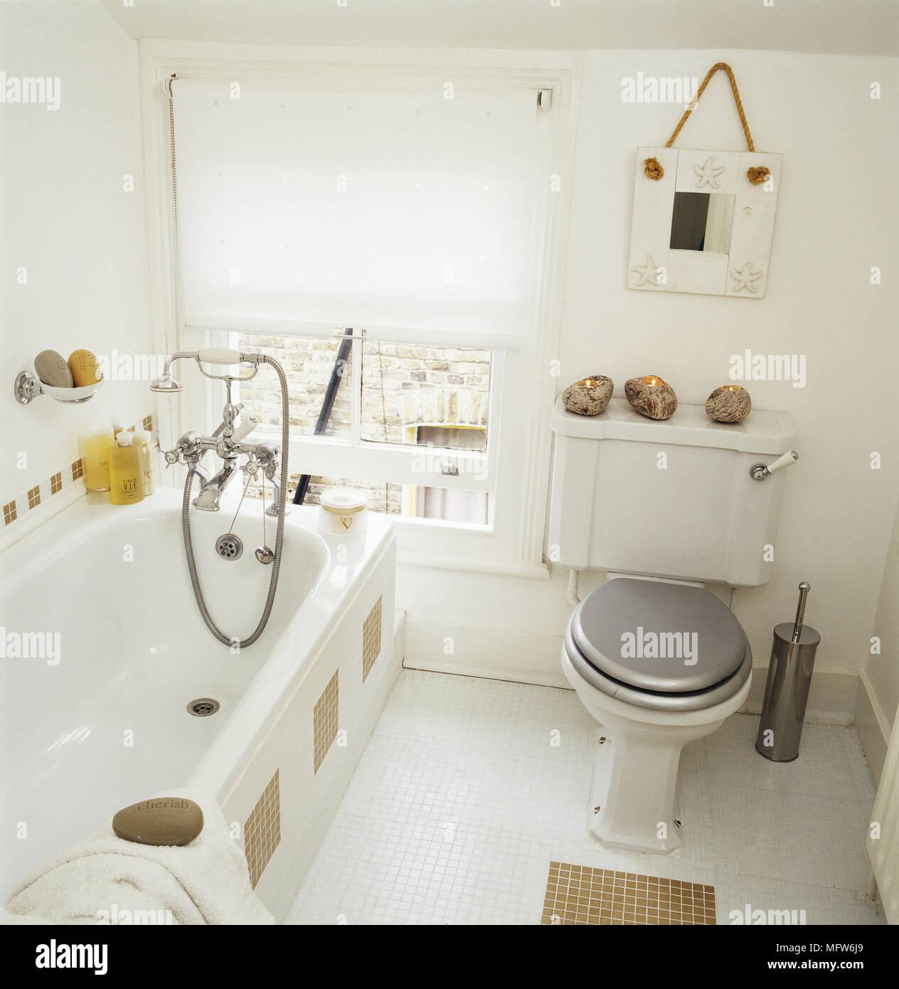 Hohe Betrachtungswinkel Und Ein Modernes Badezimmer Mit Mosaik Fliesen Wc  Badewanne Mit Duschvorrichtung Und Ein Fenster Mit Einer Walze Schatten.