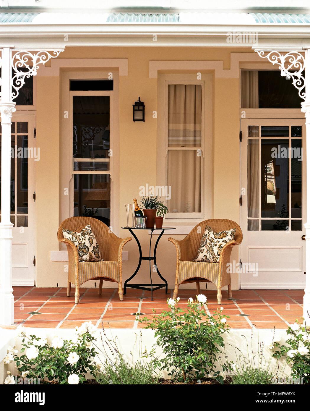 Von außen ein Bungalow mit Korbstühlen auf einer überdachten Veranda ...