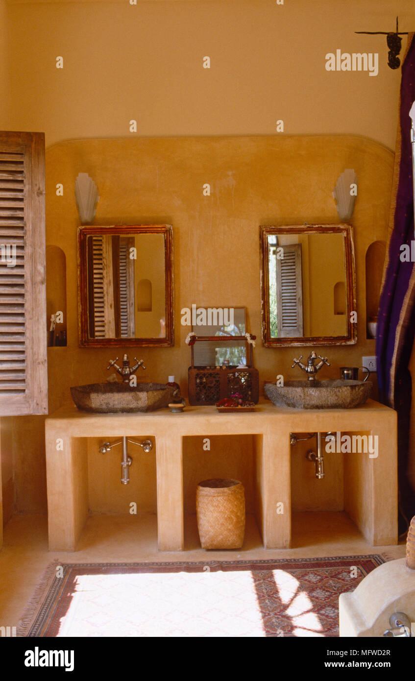 Spiegel über zwei Waschbecken auf Stein im ethnischen Stil orange ...