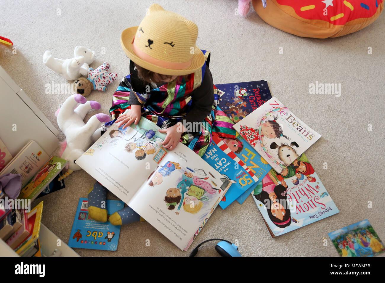 Ein Junges Mädchen, Das Lesen Von Büchern In Ihrem Schlafzimmer In Cooler,  Farbenfroher Kleidung In London, UK Gekleidet.