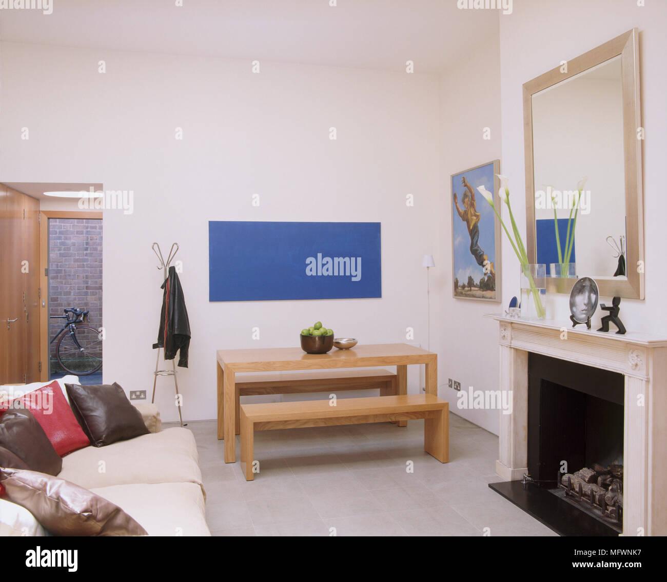 Eine Moderne, Offene Wohnzimmer Mit Kamin, Esstisch Und Sitzbänke,  Gepolstertes Sofa, Silbernen Spiegel