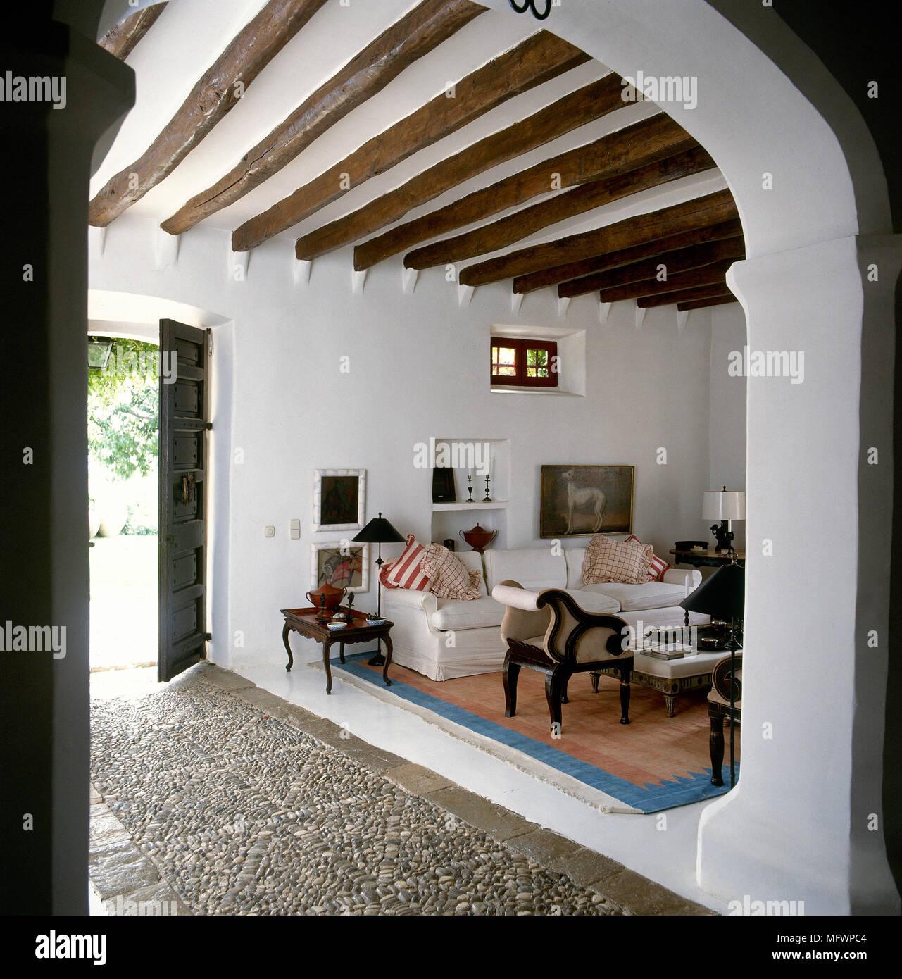 Land Stil Weiß Wohnzimmer Mit Holzbalkendecke Durch Torbogen Gesehen.
