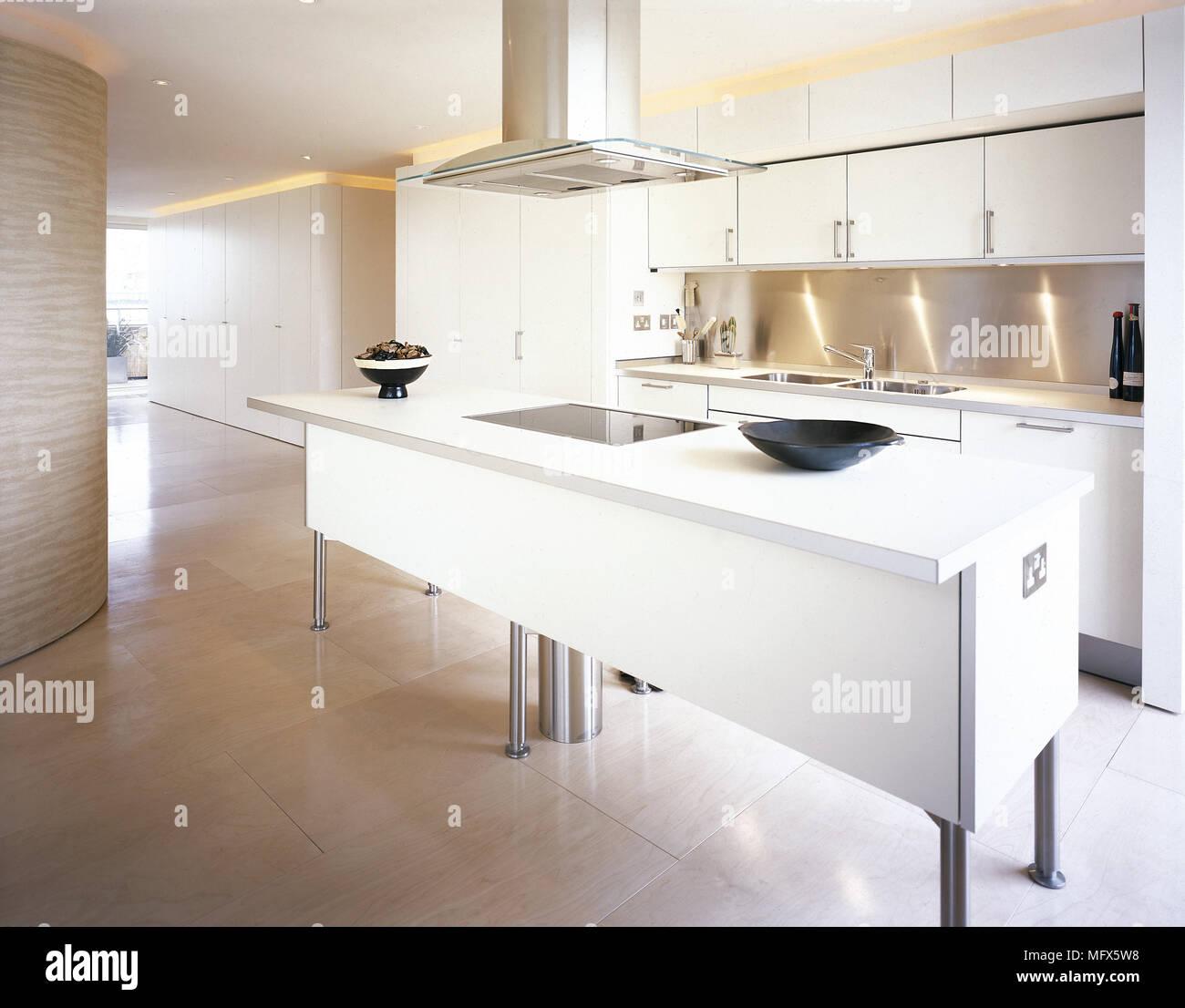 Die moderne, offene Küche mit Fliesenboden, weißen Schränken ...
