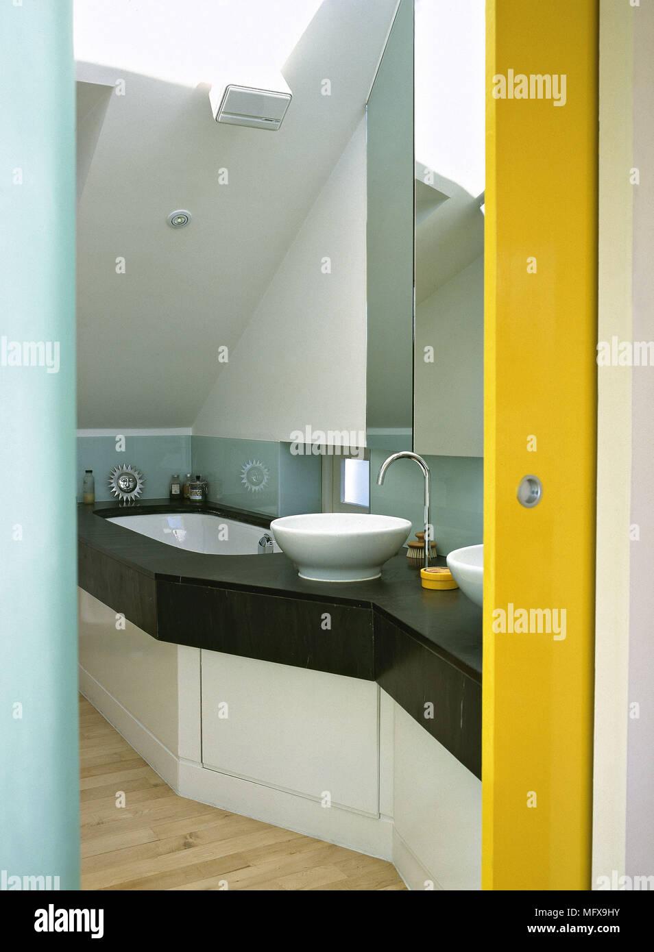 Badezimmer mit gelben Schiebetür und zwei Waschbecken auf einem ...