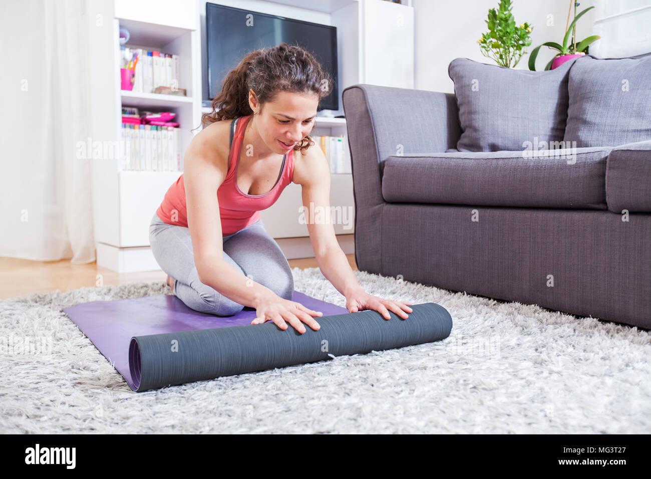junge frau falten yoga matte zu hause die vorbereitung auf die bung gesunden lebensstil. Black Bedroom Furniture Sets. Home Design Ideas