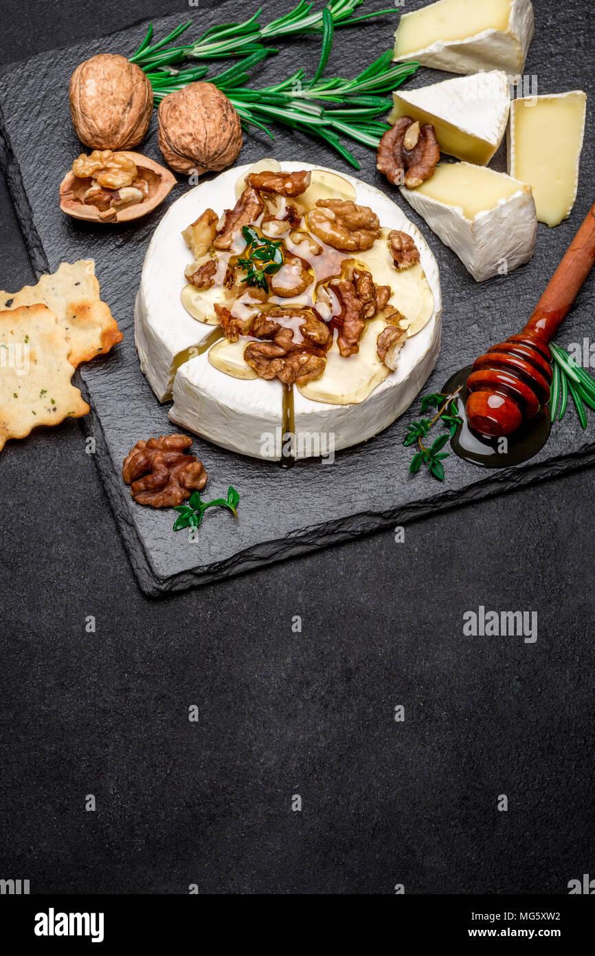 Camembert Käse und Walnüssen auf Stein Bord Stockbild