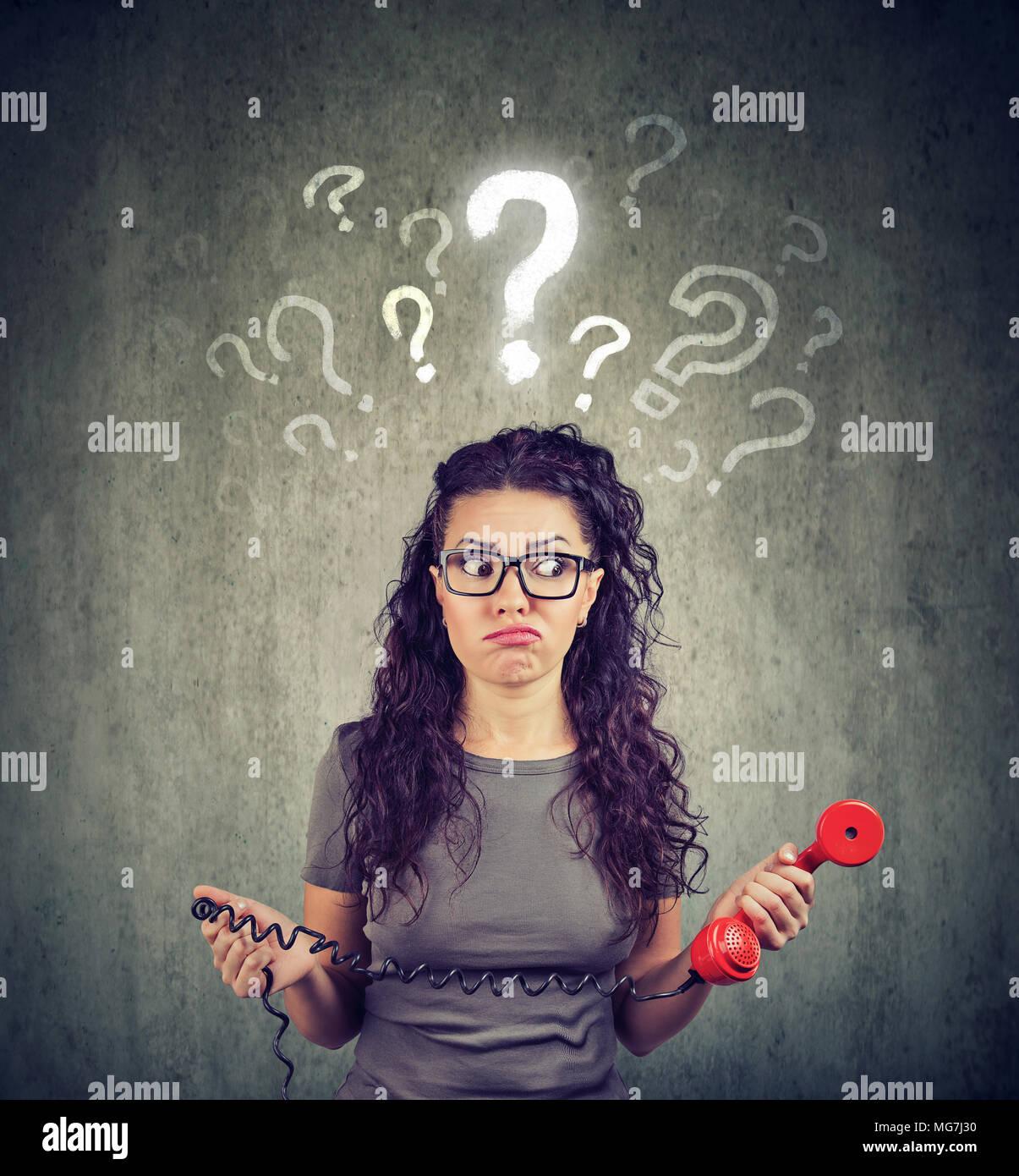 Missverständnisse und fernen rufen. Verärgert besorgt verwirrt Frau sprechen auf einem Telefon hat viele Fragen auf grauem Hintergrund. Stockbild