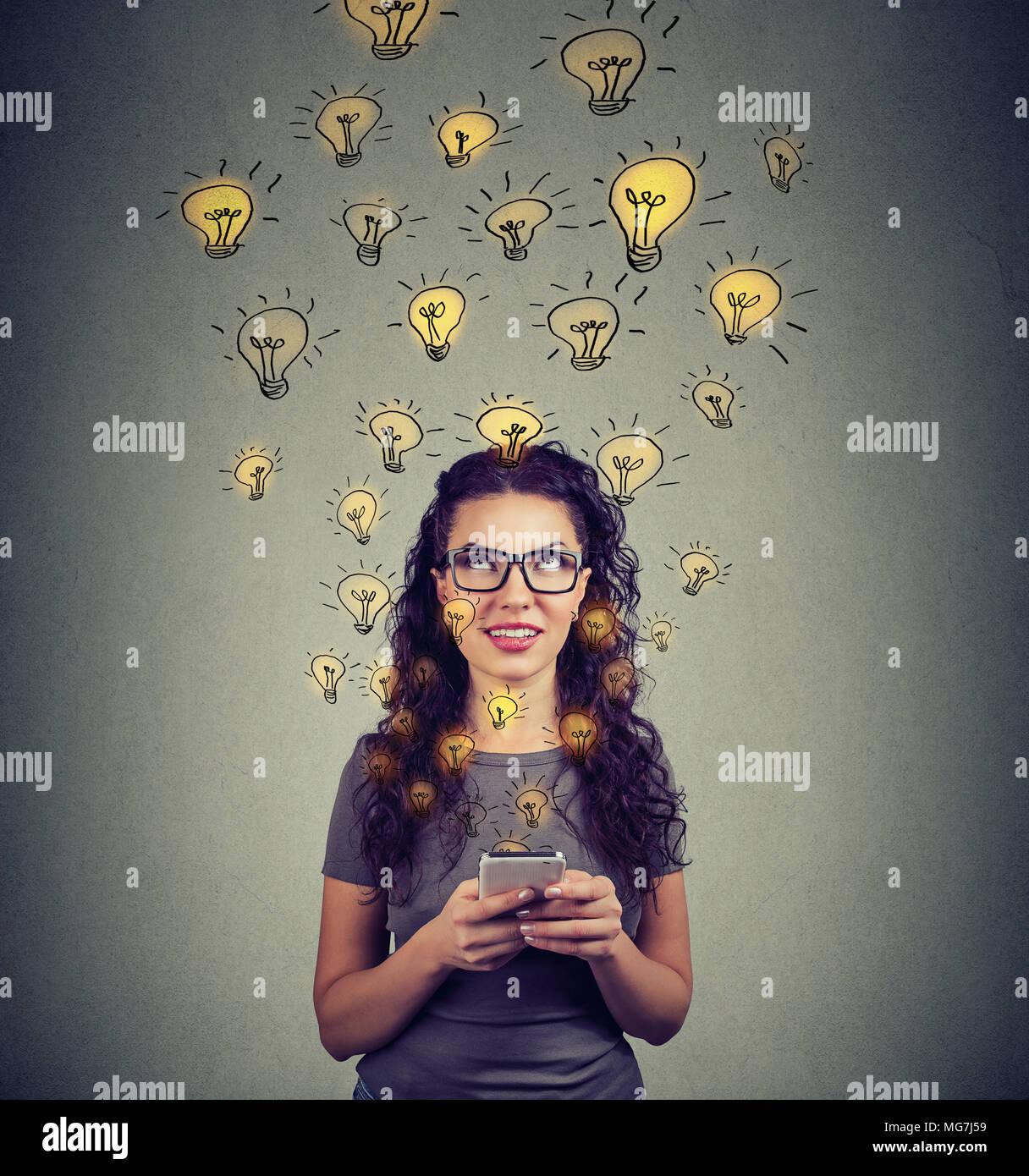Junge Frau in Brillen holding Smartphone hat viele erfolgreiche Ideen. Stockbild
