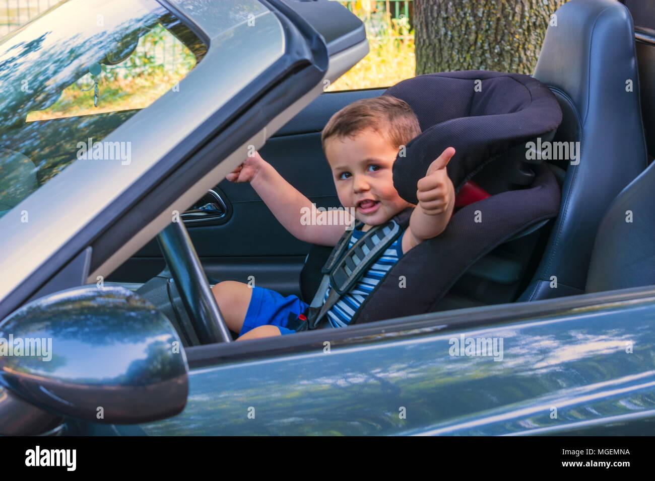 Glückliches lachendes Kind in einem Cabrio sitzt im Auto Kindersitz und zeigt den Daumen nach oben. Stockbild