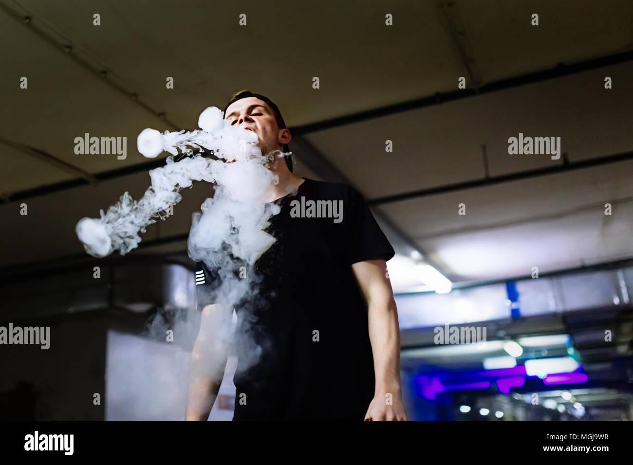 Mann in Gap Rauch eine elektronische Zigarette und Releases Wolken von Dampf Ausführen verschiedener Art vaping Tricks Stockbild