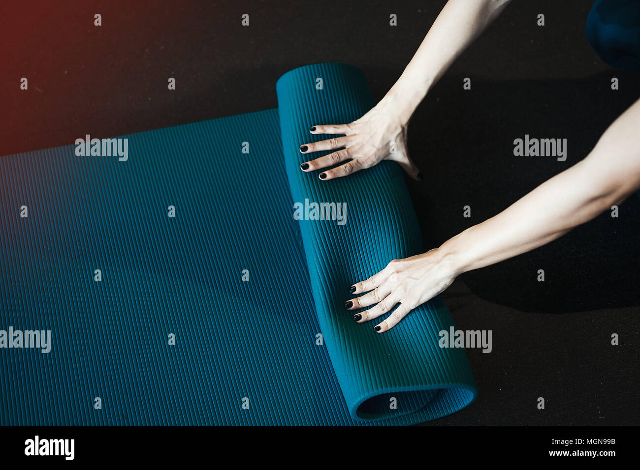 Junge Mädchen Anmeldung blau Yogamatte nach dem Üben Workout und crossfit. Stockbild
